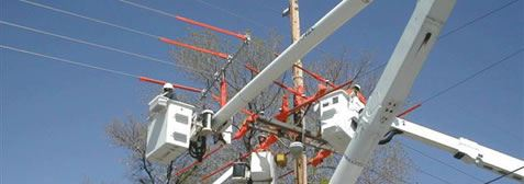 Workers in Cherrypickers Working on Electric Lines
